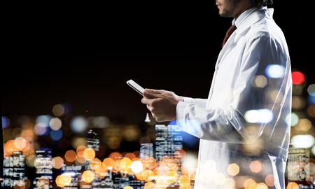 Double exposure of confident doctor in white sterile coat and night modern cityscape view on background. Concept of modern medical industry