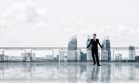 Young businessman in suit at balcony against morning cityscape background