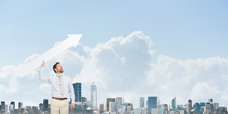 Conceptual image of attractive businessman launching huge white arrow to the sky while standing against modern cityscape view on background. Foto de archivo