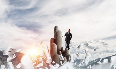 Horizontal shot of young and confident businessman in suit pointing away with white big arrow while standing on stone column with cloudy skyscape view on background. Foto de archivo