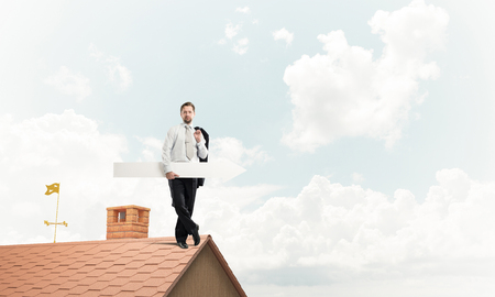 Young and ambitious businessman in suit holding big white arrow in hand and pointing away while standing on brick roof with cloudy skyscape view on background.