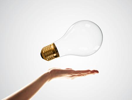 Close of male palm holding glass light bulb on white background Фото со стока