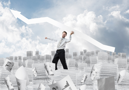 Successful development of new startup project by means of big white arrow in businessmans hand standing on columns of documents with cloudy skyscape view on background. Foto de archivo