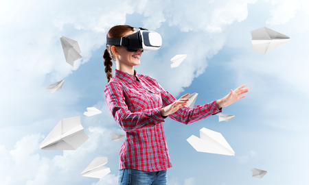 Young caucasian woman in virtual reality helmet against sky background Banco de Imagens