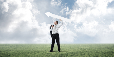 Successful and confident businessman in suit starting launching huge white arrow to the air while standing on green lawn and cloudy skyscape view on background Stockfoto