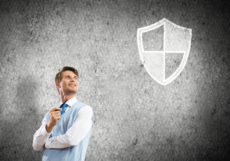 Confident and young businessman smoking pipe and drawn shield on gray wall background