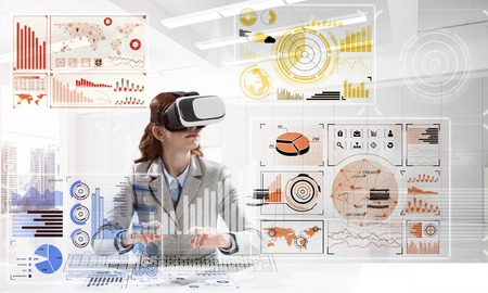Horizontal shot of young successful business woman sitting inside office and using virtual reality headset with digital media interface