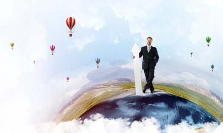 Confident and young businessman in suit holding big white arrow in hand which pointing aside while standing on Earth globe and sky view on background. Stock Photo