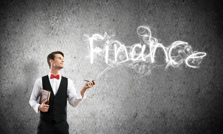 Horizontal shot of confident and young businessman in smart-casual wear smoking pipe while standing against gray dark wall and finance word made from smoke on background. Imagens - 109463647