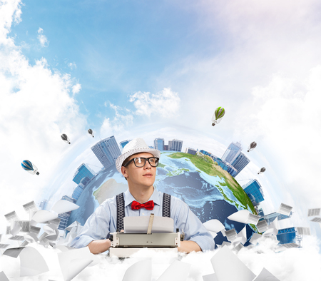 Portrait of handsome man writer in bow-tie and hat looking away while working with typing machine at the table with flying papers and Earth globe among cloudy skyscape on background. Stock Photo