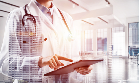 Young female doctor in white sterile coat touching tablet screen while standing at hospital building. Digital technologies for medical employee. Double exposure Stock Photo