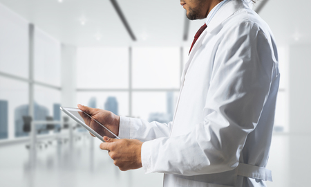 Cropped image of confident doctor in white sterile coat standing inside white hospital office building