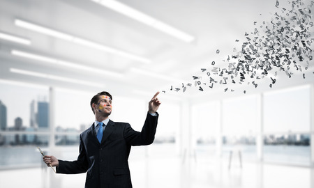 Conceptual image of cheerful and young businessman in black suit gesturing and smiling while standing near flying letters inside bright modern office. 스톡 콘텐츠