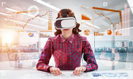 Technologies modernes pour l'éducation au moyen d'une jeune étudiante en chemise à carreaux utilisant des lunettes de réalité virtuelle et interagissant avec l'interface des médias numériques. Banque d'images