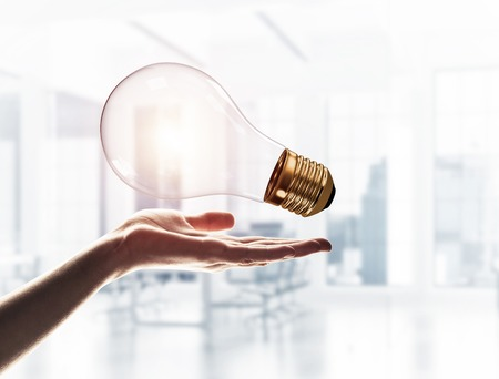 Close of male palm holding glass light bulb on interior background Фото со стока