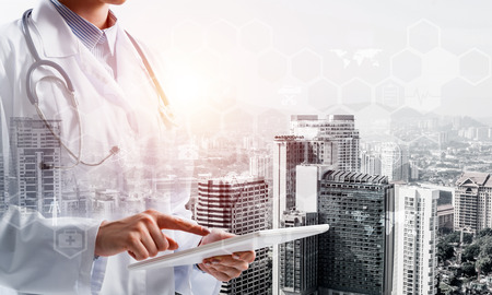 Double exposure of young woman doctor in white medical uniform touching tablet with her finger and city view and modern interface on background, Conceptual image of modern medical industry
