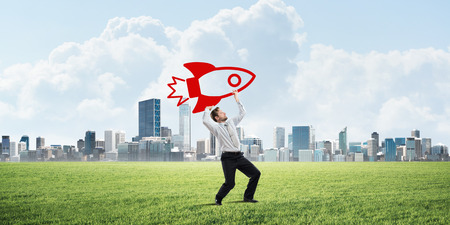 Horizontal shot of successful and young businessman standing on green lawn and throwing huge rocket in the air with modern city view on background Stock Photo
