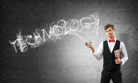 Horizontal shot of confident and young businessman in smart-casual wear smoking pipe while standing against gray dark wall and technology word made from smoke on background. Imagens - 110220069