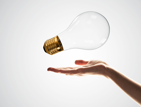 Close of male palm holding glass light bulb on white background Stock Photo