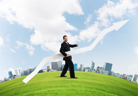Conceptual image of young successful business man in black suit pointing aside by means of big white banner in form of arrow while standing on green meadow with city on background. Stock Photo