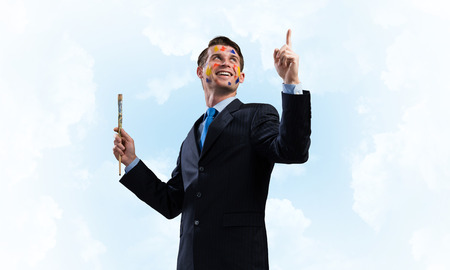 Portrait of young and happy businessman in black suit gesturing and smiling while standing against blue cloudy skyscape on background.