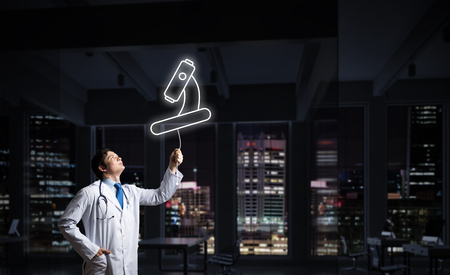 Conceptual image of young male doctor in white uniform interracting with glowing microscope icon in the air while standing against night cityscape view on background.