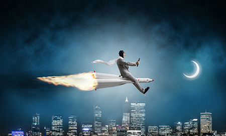 Conceptual image of young businessman in suit flying on rocket with night cityscape and blue dark sky with moon on background.