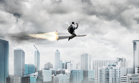 Conceptual image of young businessman in suit flying on rocket with modern cityscape with skyscrapers and blue sky on background.