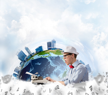 Side view of hard-working man writer using typing machine while sitting at the table with flying letters and Earth globe among cloudy skyscape on background.
