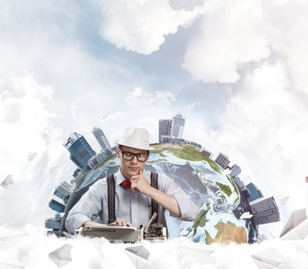 Portrait of young man writer in hat and eyeglasses looking away and touching chin while sitting among flying paper planes and with Earth globe among cloudy skyscape on background. Stock Photo