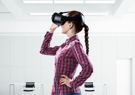 Young caucasian woman in modern office interior trying virtual reality helmet. Mixed media
