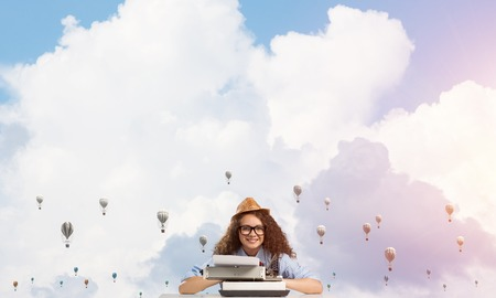 Young and beautiful woman writer in hat and eyeglasses using typing machine while sitting at the table with flying aerostats and cloudy skyscape on background.