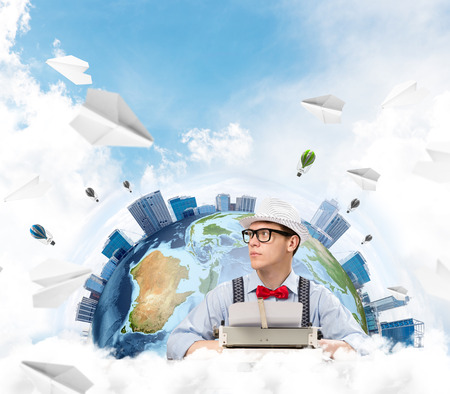 Handsome man writer in bow-tie and hat looking away while working with typing machine at the table with flying paper planes and Earth globe among cloudy skyscape on background.