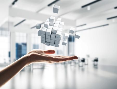 Fine della figura del cubo della tenuta della mano dell'uomo d'affari come simbolo di innovazione. Rendering 3D