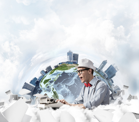 Emotional young man writer in hat and eyeglasses feeling surprised while using typing machine at the table with flying papers and Earth globe among cloudy skyscraper on background.