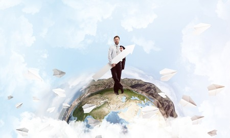 Young and confident businessman in suit holding big white arrow in hand and pointing aside while standing on Earth globe with cloudy sky on background. Foto de archivo