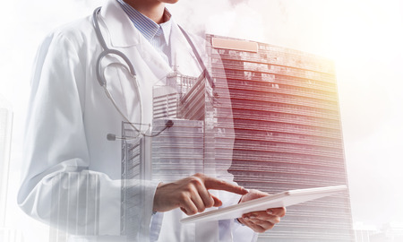 Cropped image of young female doctor in white sterile coat using tablet while standing outdoors with cityscape on background. Medical industry concept. Double exposure