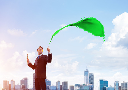 Cheerful and young businessman in black suit gesturing and smiling while standing with green liquid splash against cityscape view on background. 스톡 콘텐츠