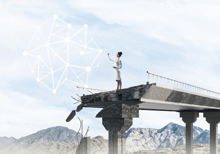 Professional medical industry employee in white uniform using tablet while standing at end of broken bridge and examining social network structure. Medical industry concept. Landscape on background