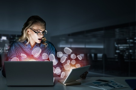 Surprised beautiful girl looking in glowing laptop screen and flying chat icons. Mixed media Stock Photo
