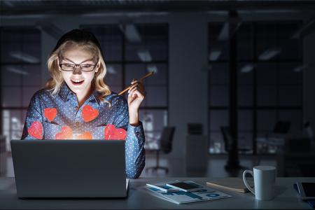 Surprised beautiful girl looking in glowing laptop screen. Mixed media Stock Photo