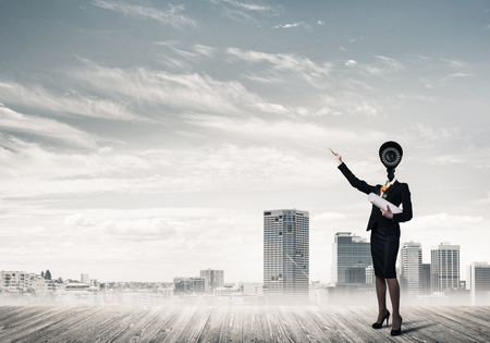 Faceless businesswoman with camera zoom instead of head against cityscape background