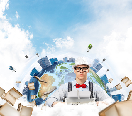 Young man writer in hat and eyeglasses using typing machine while sitting at the table with flying books and Earth globe among cloudy skyscape on background. Elements of this image furnished by NASA Stock Photo