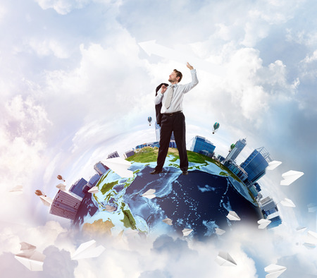 Successful business man in suit holding huge white arrow in hand while standing on Earth globe with cloudy skyscraper view on background.