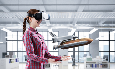 Young caucasian woman in modern office interior trying virtual reality helmet and viewing space shuttle. Mixed media Stock Photo