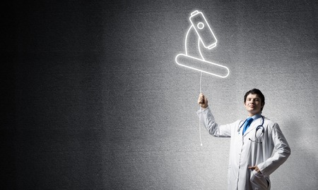 Young male doctor in white uniform interracting with glowing microscope icon in the air while standing against gray dark wall on background.
