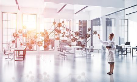 Confident medical industry employee in white suit standing inside bright hospital building and interracting with social media network structure Stock Photo