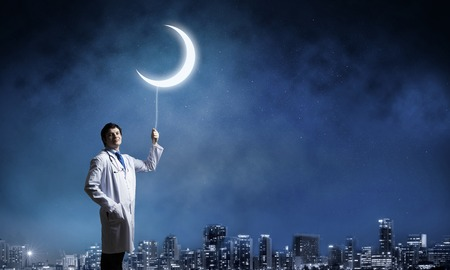 Cheerful doctor in white medical uniform keeping young moon on the rope while standing against night city view and dark blue sky on background.