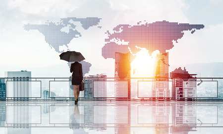 Back view of businesswoman with black umbrella looking at city. Mixed media Stock Photo
