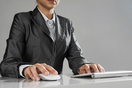 Close up of businesswoman hand typing on keyboard with mouse on wood table Stock Photo